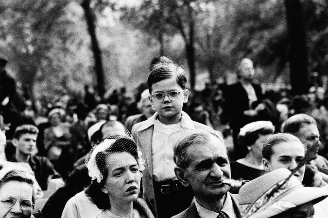 Niño arriba de una multitud